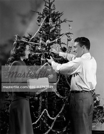 1940s COUPLE DECORATING CHRISTMAS TREE WITH CHRISTMAS BALLS