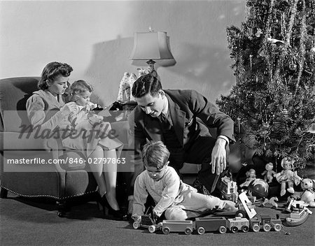 1930s 1940s FAMILY AROUND CHRISTMAS TREE BOY PLAYING WITH TRAIN DAD HELPING MOM Stock Photo - Rights-Managed, Image code: 846-02797863