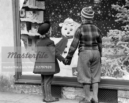 1930s BOY AND GIRL HOLDING HANDS LOOKING AT DECORATED CHRISTMAS WINDOW Stock Photo - Rights-Managed, Image code: 846-02797920