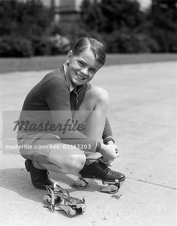 1930s SMILING BOY FASTENING ON STREAMLINE METAL ROLLER SKATES Stock Photo - Rights-Managed, Image code: 846-03163203