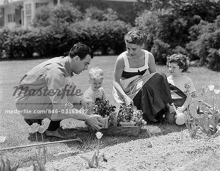 1950s FAMILY IN GARDEN PLANTS FLOWERS