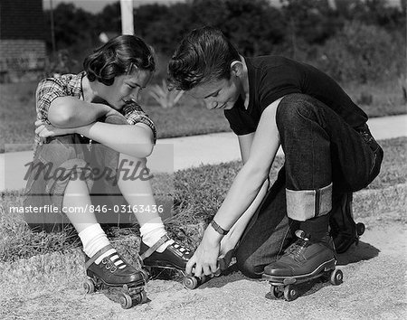 1950s BOY AND GIRL PUTTING ON ROLLER-SKATES SITTING ON SIDEWALK Stock Photo - Rights-Managed, Image code: 846-03163436