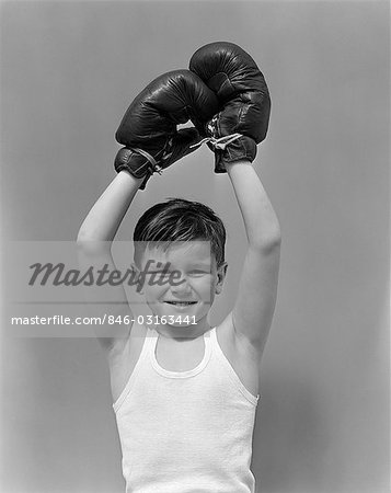 1940s CHILD WEARING BOXING GLOVES HOLDING HANDS ABOUT HEAD Stock Photo - Rights-Managed, Image code: 846-03163441