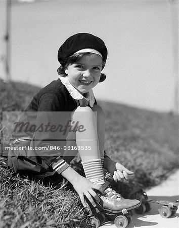 1930s CHILD PUTTING ON ROLLER-SKATE SITTING Stock Photo - Rights-Managed, Image code: 846-03163535