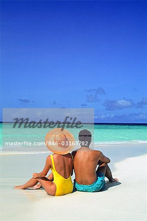 1990s MAN AND WOMAN SITTING ON THE BEACH FACING THE WATER MOPION ISLAND, GRENADINES, WEST INDIES Stock Photo - Rights-Managed, Image code: 846-03163782