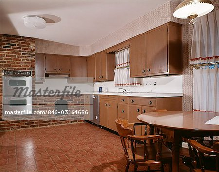 1970s KITCHEN WITH DARK WOODEN CABINETS BRICK WALL AND DOUBLE OVEN Stock Photo - Rights-Managed, Image code: 846-03164686