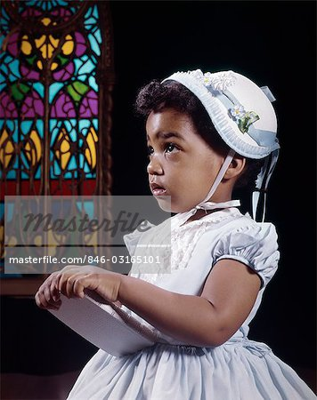 1960s RELIGIOUS LITTLE AFRICAN AMERICAN GIRL WEARING WHITE HAT AND DRESS HOLDING BIBLE STANDING BY STAINED GLASS WINDOW IN CHURCH Stock Photo - Rights-Managed, Image code: 846-03165101