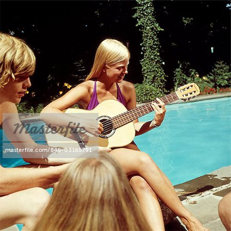 1970s TEEN GIRL PLAYING GUITAR SWIMMING POOL PARTY