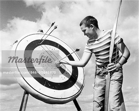 1960s BOY JEANS STRIPED T-SHIRT HOLDING BOW & PULLING ARROW OUT OF TARGET BULL'S-EYE Stock Photo - Rights-Managed, Image code: 846-05645870