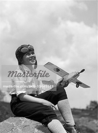 1930s BOY IN LEATHER AVIATOR CAP WITH GOGGLES SITTING ON ROCK HOLDING MODEL PLANE Stock Photo - Rights-Managed, Image code: 846-05645948