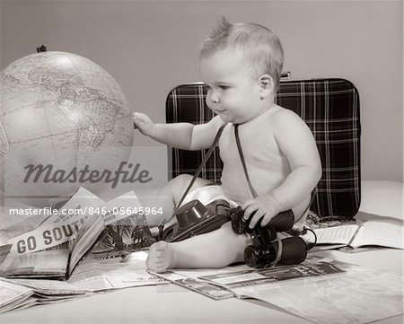 1960s BABY SEATED LOOKING AT GLOBE WITH CAMERA BINOCULARS SUITCASE & TRAVEL BROCHURES Stock Photo - Rights-Managed, Image code: 846-05645964