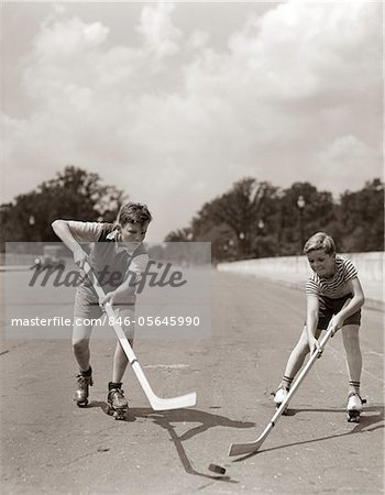 1930s - 1940s 2 BOYS WITH STICKS AND PUCK WEARING ROLLER SKATES PLAYING STREET HOCKEY Stock Photo - Rights-Managed, Image code: 846-05645990