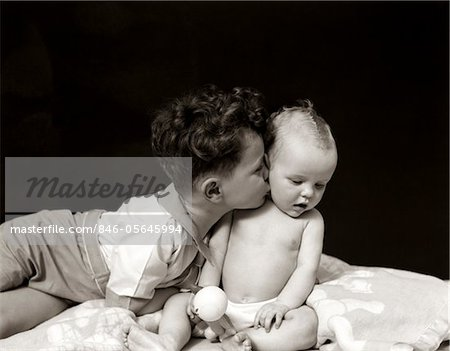 1940s CURLY HAIRED BOY TODDLER LEANING AND KISSING CUTE BABY Stock Photo - Rights-Managed, Image code: 846-05645994