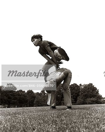 1970s PAIR OF BOYS OUTSIDE IN FIELD PLAYING LEAPFROG Stock Photo - Rights-Managed, Image code: 846-05646070