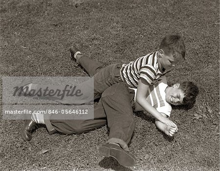 1950s TWO BOYS WEAR TEE SHIRTS BLUE JEANS PLAYING ROUGH FIGHTING WRESTLING ON THE GRASS Stock Photo - Rights-Managed, Image code: 846-05646112