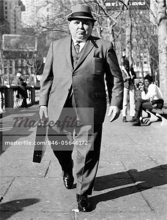 1960s OVERWEIGHT BUSINESSMAN WITH BRIEFCASE SMOKING CIGAR WALKING ON CITY SIDEWALK Stock Photo - Rights-Managed, Image code: 846-05646172