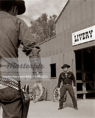 1950s - 1960s TV COWBOYS IN FRONT OF LIVERY STABLE READY TO DRAW PISTOLS IN GUNFIGHT Stock Photo - Rights-Managed, Image code: 846-05646221