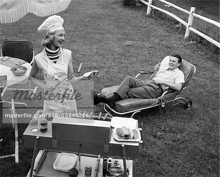 1950s - 1960s WOMAN IN CHEF'S HAT AND APRON GRILLING HOT DOGS ON GRILL MAN IN CHAISE LONGUE LAUGHING EATING A FRANKFURTER OUTSIDE