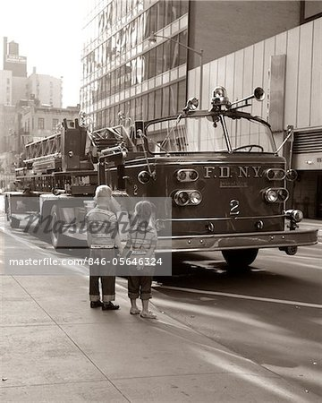 1970s 2 CHILDREN BOY GIRL HOLDING HANDS LOOKING AT FIRE TRUCK PARKED ON STREET NEW YORK CITY Stock Photo - Rights-Managed, Image code: 846-05646324