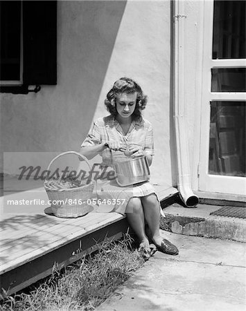 1940s WOMAN WEARING PLAID DRESS AND APRON SITTING ON PORCH OF FARMHOUSE WITH BASKET OF VEGETABLES PEELING TOMATO OVER POT Stock Photo - Rights-Managed, Image code: 846-05646357