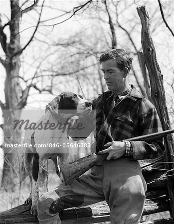 1930s MAN HUNTER WEARING PLAID FLANNEL SHIRT AND JODHPURS SITTING ON LOG HOLDING SHOTGUN PETTING POINTER DOG