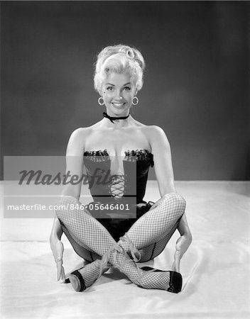 1960s BLONDE CHEESECAKE PORTRAIT OF WOMAN WEARING BLACK CAMISOLE CORSET AND FISHNET STOCKINGS Stock Photo - Rights-Managed, Image code: 846-05646401