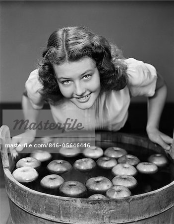 1940s SMILING TEEN GIRL LEANING OVER TUB ABOUT TO BEGIN BOBBING FOR APPLES FLOATING IN THE WATER Stock Photo - Rights-Managed, Image code: 846-05646446