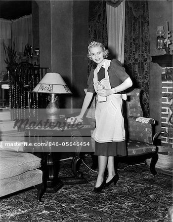 1940s BLONDE WOMAN HOUSEWIFE MAID WEARING APRON CLEANING POLISHING WOODEN END TABLE IN ORNATE LIVING ROOM Stock Photo - Rights-Managed, Image code: 846-05646454