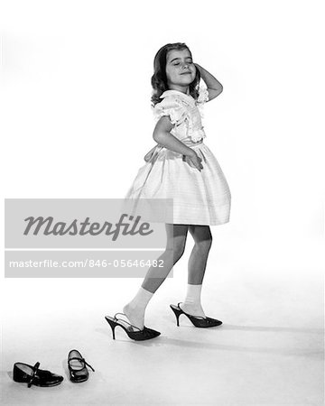 1960s GIRL MAKING GLAMOUR POSE HAVING STEPPED OUT OF HER SHOES INTO HER MOTHERS ADULT HIGH HEELS Stock Photo - Rights-Managed, Image code: 846-05646482