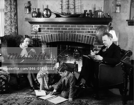 1930s FAMILY OF FOUR SITTING IN FRONT FIREPLACE MOTHER KNITTING FATHER READING SMOKING PIPE KIDS DOING HOMEWORK Stock Photo - Rights-Managed, Image code: 846-05646502