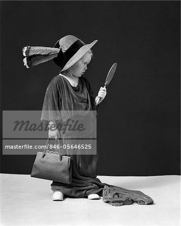 1930s - 1940s GIRL PLAYING DRESS-UP LOOKING AT HERSELF IN HAND MIRROR Stock Photo - Rights-Managed, Image code: 846-05646525