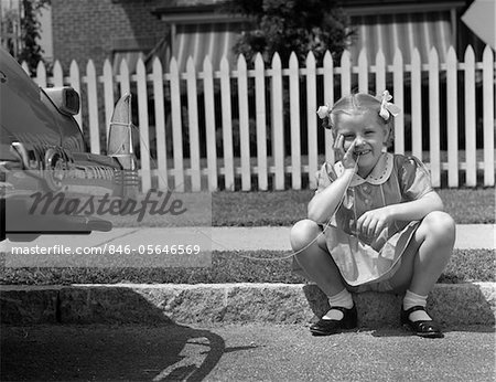 1940s GIRL SITTING ON CURB WITH TOOTH TIED TO BACK OF CAR FENDER Stock Photo - Rights-Managed, Image code: 846-05646569