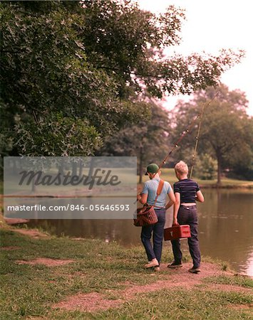 1970s TWO BOYS WALKING BESIDE POND CARRYING FISHING POLES AND TACKLE Stock Photo - Rights-Managed, Image code: 846-05646593