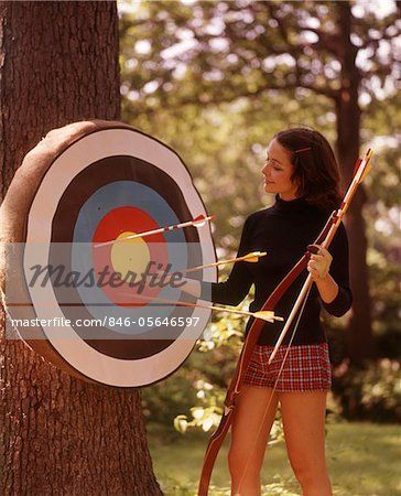 1970s WOMAN FEMALE ARCHER PULLING ARROWS FROM ARCHERY TARGET Stock Photo - Rights-Managed, Image code: 846-05646597