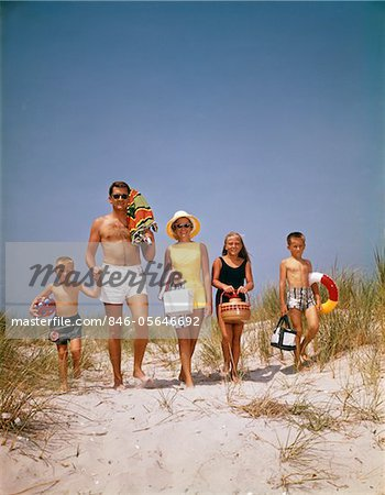 1960s FAMILY WALKING TOGETHER TO THE BEACH OVER SAND DUNES  CARRY PICNIC AND BEACH GEAR Stock Photo - Rights-Managed, Image code: 846-05646692