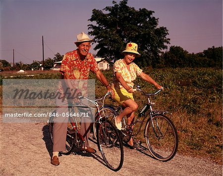 1970s SENIOR ELDERLY RETIRED COUPLE RIDING BIKES WEARING STRAW HATS HAWAIIAN PRINT SHIRTS Stock Photo - Rights-Managed, Image code: 846-05646711