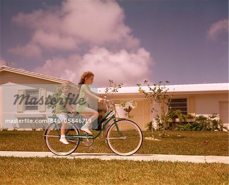 1970s GIRL RIDING BIKE ON SUBURBAN STREET BOY RIDES PIGGY BACK Stock Photo - Rights-Managed, Image code: 846-05646719