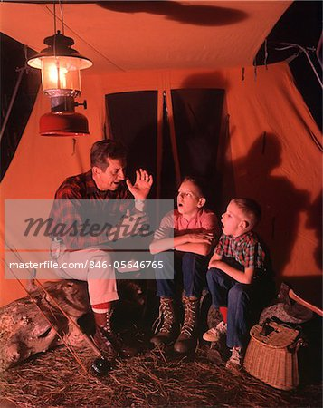 1960s - 1970s  GRANDFATHER TELLING SCARY STORY TO BOYS BY TENT AT NIGHT CAMPSITE IN SHADOWS Stock Photo - Rights-Managed, Image code: 846-05646765