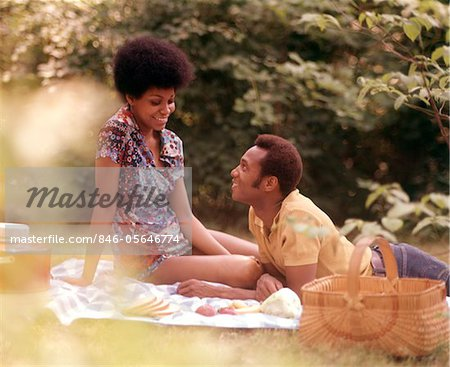 1970s ROMANTIC AFRICAN-AMERICAN COUPLE MAN WOMAN PICNIC BASKET SITTING GRASS Stock Photo - Rights-Managed, Image code: 846-05646774
