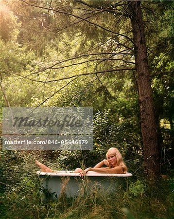 1970s SMILING NUDE BLOND WOMAN SITTING IN ANTIQUE IRON BATHTUB IN A FOREST GLEN Stock Photo - Rights-Managed, Image code: 846-05646979
