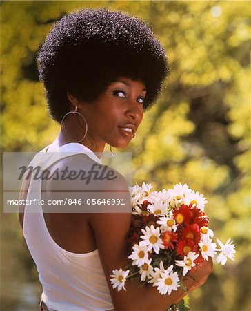 1970s SMILING AFRICAN-AMERICAN WOMAN WEARING HOOP EARRINGS WHITE TANK TOP HOLDING A BOUQUET SPRING FLOWERS Stock Photo - Rights-Managed, Image code: 846-05646991