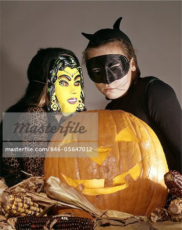 TWO YOUNG GIRLS IN WITCH AND BLACK CAT HALLOWEEN COSTUMES WITH CARVED JACK-O-LANTERN PUMPKIN S Stock Photo - Rights-Managed, Image code: 846-05647012