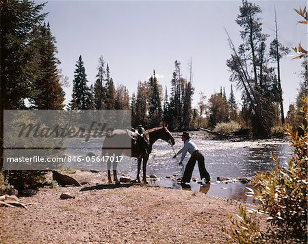 1970s COWBOY STANDING IN STREAM LEADING HORSE BY REINS TO WATER Stock Photo - Rights-Managed, Image code: 846-05647017