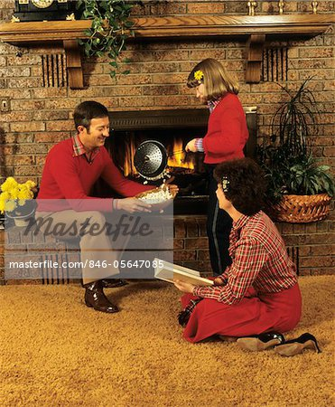1970s - 1980s FAMILY FATHER MOTHER DAUGHTER SITTING BY FIREPLACE POPPING CORN Stock Photo - Rights-Managed, Image code: 846-05647085