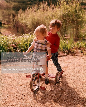 1960s - 1970s YOUNG BOY AND GIRL PLAYING TOGETHER RIDING TRICYCLE Stock Photo - Rights-Managed, Image code: 846-05647143