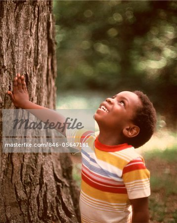 1970s SMILING AFRICAN-AMERICAN BOY LOOKING UP TREE TRUNK WEARING  STRIPED TEE SHIRT Stock Photo - Rights-Managed, Image code: 846-05647161