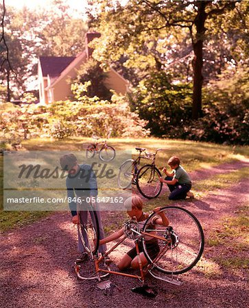 1970s 3 BOYS BACKYARD DRIVEWAY SUBURBAN HOUSE WORK ON BICYCLE MAINTENANCE REPAIR Stock Photo - Rights-Managed, Image code: 846-05647162