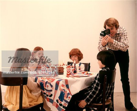 1970s FATHER WITH HOME MOVIE CAMERA TAKING PICTURES BIRTHDAY PARTY CHILDREN AT TABLE Stock Photo - Rights-Managed, Image code: 846-05647164