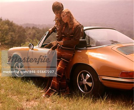 1970s STYLISHLY DRESSED COUPLE STANDING TOGETHER LEANING ON A CONVERTIBLE PORSCHE AUTOMOBILE SPORTS CAR Stock Photo - Rights-Managed, Image code: 846-05647207