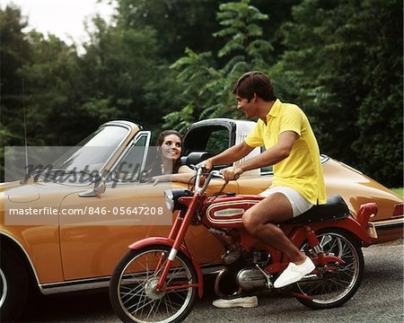1970s LIFESTYLE TALKING FLIRT COUPLE MAN ON SMALL RED HARLEY DAVIDSON MOTORCYCLE SMILING WOMAN IN ORANGE PORSCHE AUTOMOBILE Stock Photo - Rights-Managed, Image code: 846-05647208